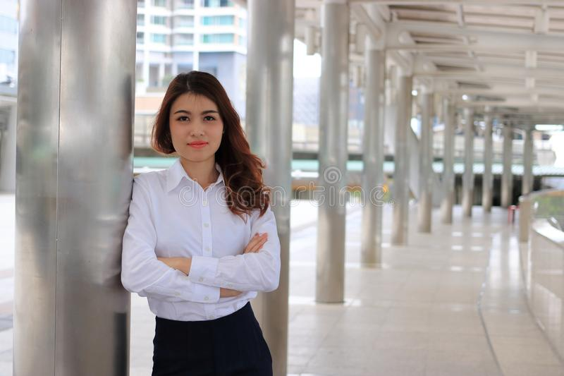 Retrato de la mujer de negocios asiática atractiva joven que inclina un polo en fondo urbano del edificio fotos de archivo
