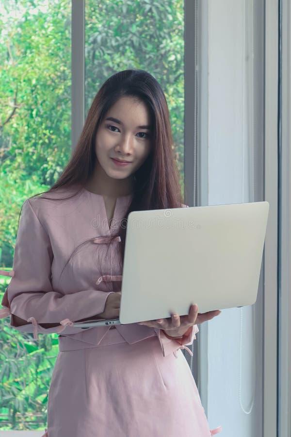 Retrato de la mujer de negocios asiática hermosa y atractiva joven con la sonrisa en labtop rosado del control del vestido en los imágenes de archivo libres de regalías