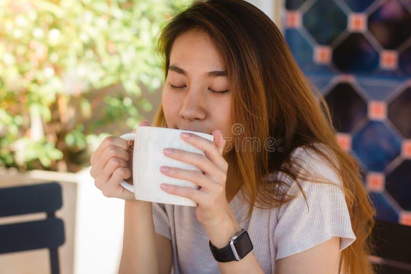 Retrato de la mujer de negocios asiática joven feliz con la taza en manos que bebe el café por la mañana en el café fotografía de archivo libre de regalías