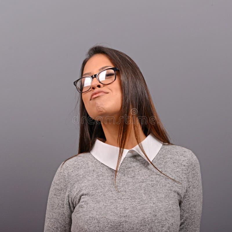 Retrato de la mujer de negocios atractiva con los vidrios contra fondo gris foto de archivo libre de regalías
