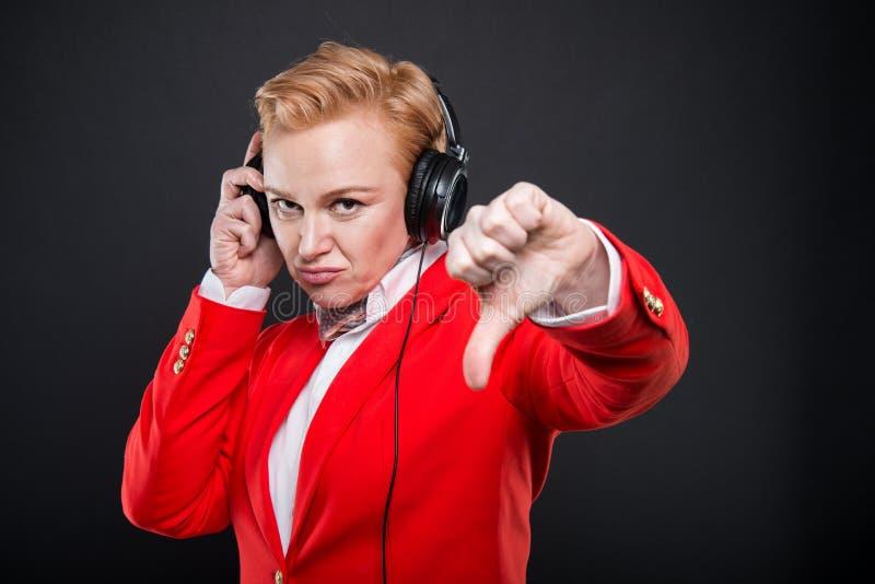 Retrato de la mujer de negocios atractiva que celebra mostrar de los auriculares fotos de archivo