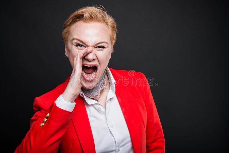 Retrato de la mujer de negocios atractiva que grita hacia fuera ruidosamente foto de archivo libre de regalías