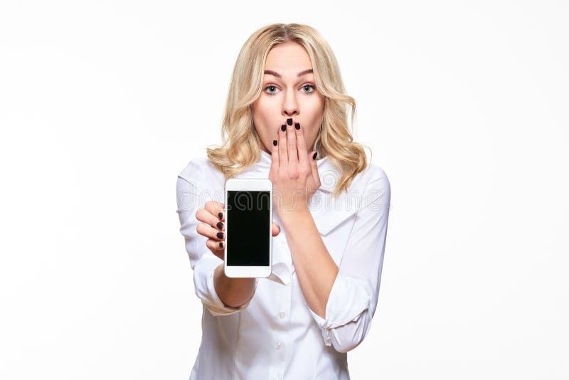 Retrato de la mujer de negocios bastante rubia chocada con la mano en su boca que muestra a teléfono móvil la pantalla en blanco  fotos de archivo libres de regalías