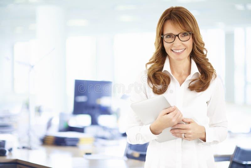 Retrato de la mujer de negocios confiada con la tableta digital imagen de archivo libre de regalías