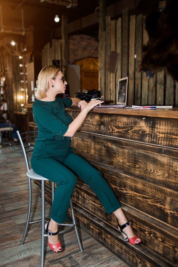 Retrato de la mujer de negocios joven bonita en los vidrios que se sientan en lugar de trabajo fotos de archivo libres de regalías