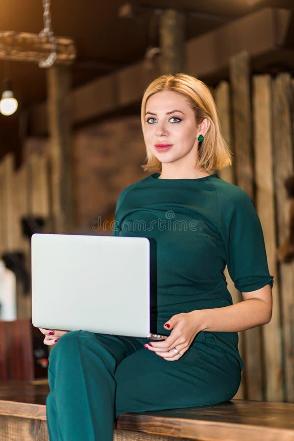 Retrato de la mujer de negocios joven bonita en los vidrios que se sientan en lugar de trabajo imagen de archivo libre de regalías
