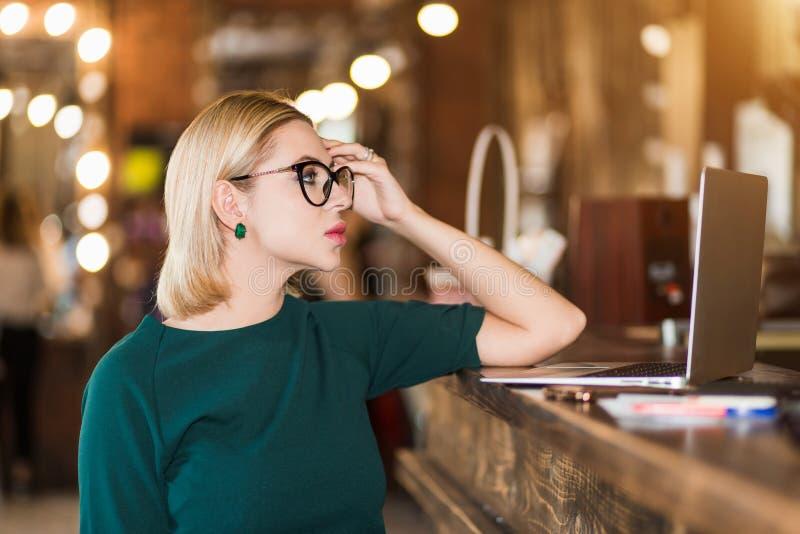 Retrato de la mujer de negocios joven bonita en vidrios en lugar de trabajo fotografía de archivo