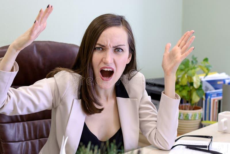 Retrato de la mujer de negocios joven enojada, de griterío en una silla de cuero detrás del escritorio de oficina fotografía de archivo libre de regalías