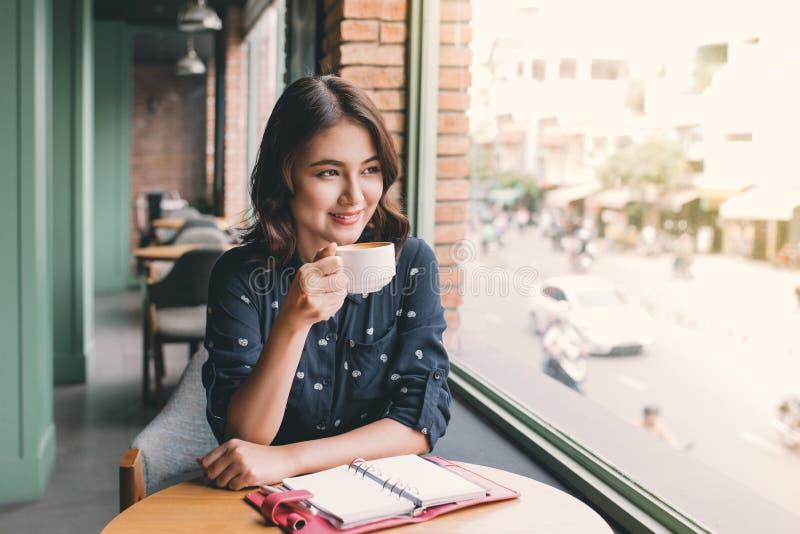 Retrato de la mujer de negocios joven feliz con la taza en drinkin de las manos fotos de archivo libres de regalías