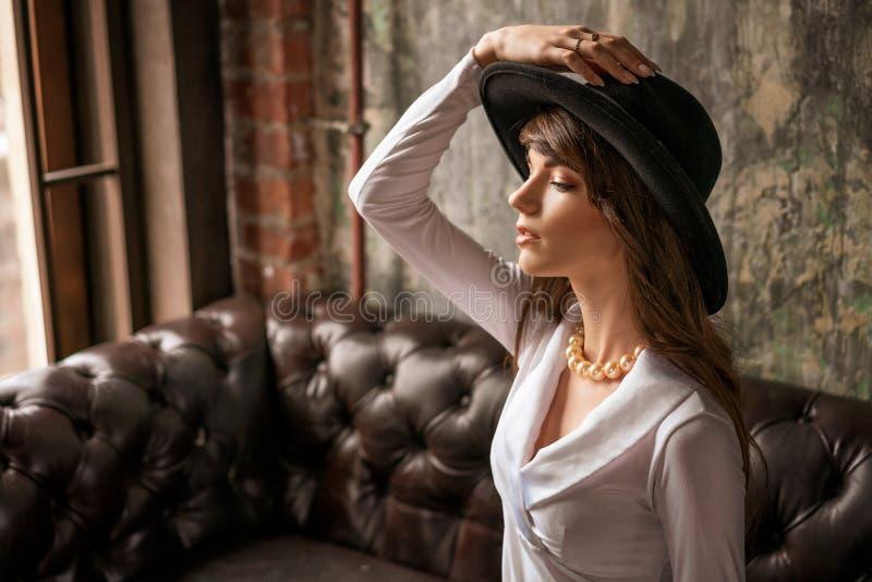 Retrato de la mujer de negocios joven hermosa en sombrero negro y la camisa blanca en el sofá de cuero foto de archivo libre de regalías