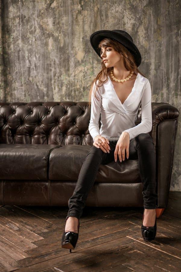 Retrato de la mujer de negocios joven hermosa en sombrero negro y la camisa blanca en el sofá de cuero fotografía de archivo libre de regalías