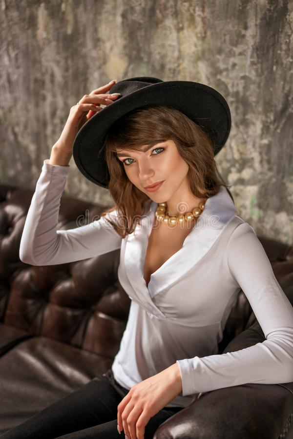 Retrato de la mujer de negocios joven hermosa en sombrero negro y la camisa blanca en el sofá de cuero imagen de archivo libre de regalías