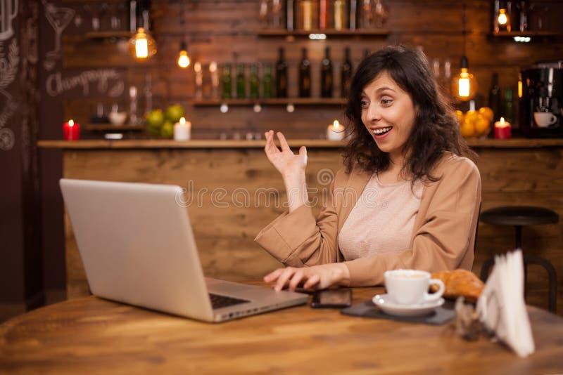 Retrato de la mujer de negocios sorprendida en una llamada video en una cafetería moderna imagenes de archivo