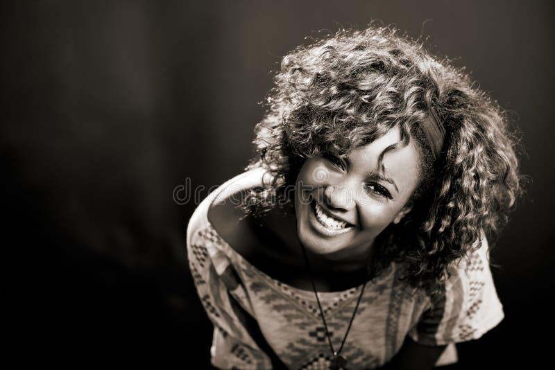 Mujer negra hermosa en fondo negro. Tiro del estudio imagenes de archivo