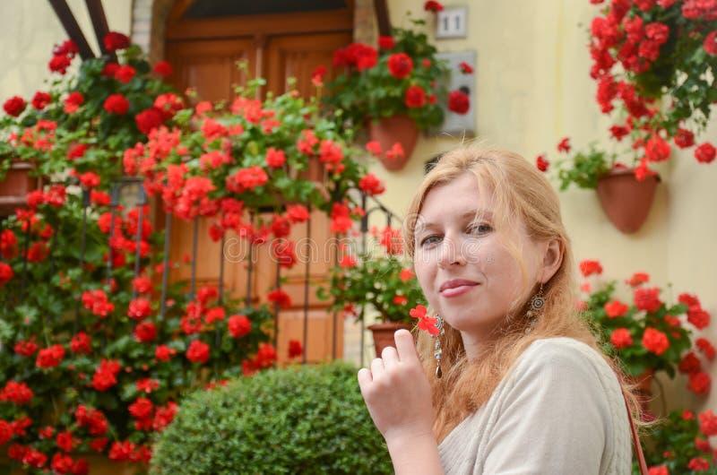 Retrato de la mujer pelirroja delante de las flores rojas imagen de archivo libre de regalías