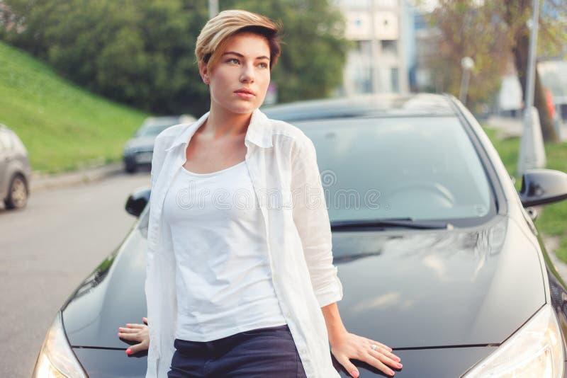 Retrato de la mujer pensativa joven elegante que se inclina en el coche fotos de archivo