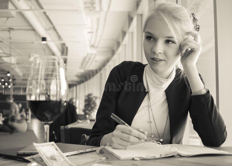 Retrato de la mujer pensativa joven que trabaja sobre la copa de vino foto de archivo