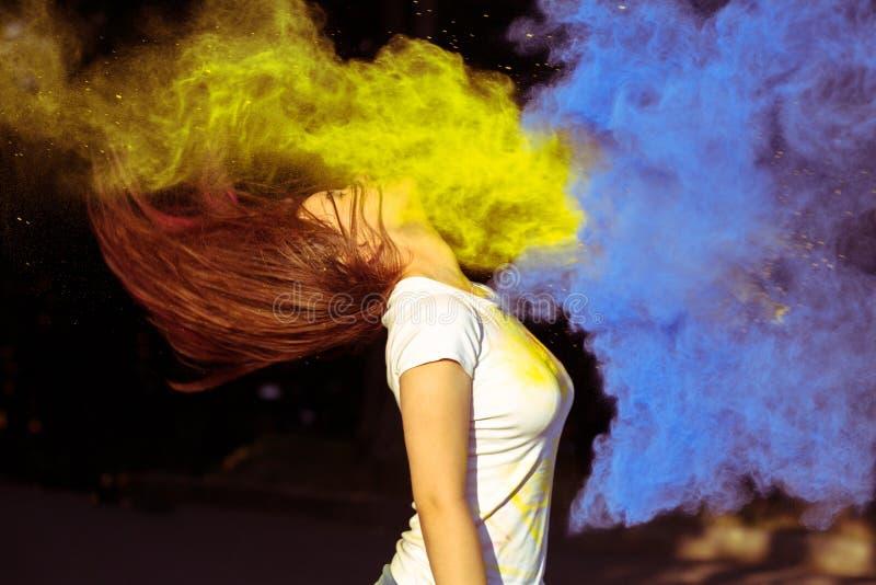 Retrato de la mujer preciosa con soplar el polvo seco Holi del color en t imagen de archivo