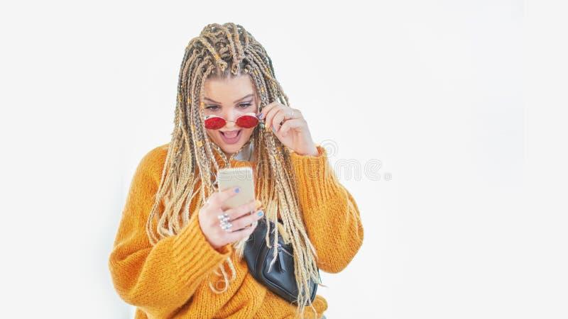 Retrato de la mujer preguntada, estudiante emocionado, novia chocada que tiene teléfono móvil elegante del teléfono en manos mira fotos de archivo