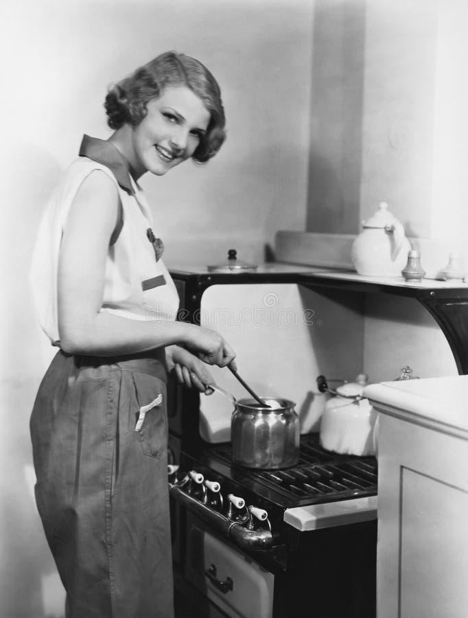 Retrato de la mujer que cocina en la estufa foto de archivo libre de regalías