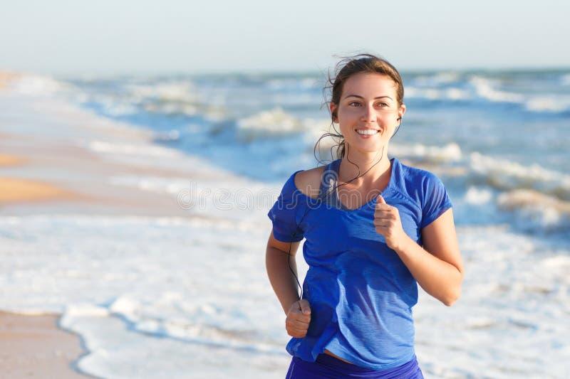 Retrato de la mujer que corre por la playa del océano o del mar fotos de archivo libres de regalías