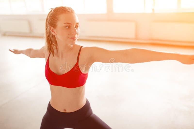 Retrato de la mujer que estira sus brazos y que mira lejos el gimnasio imagen de archivo libre de regalías