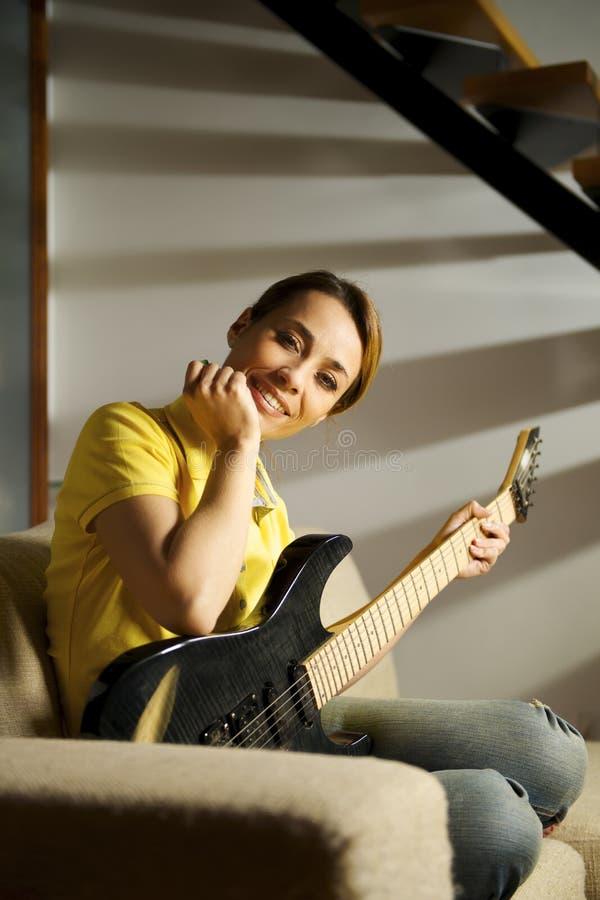 Retrato de la mujer que juega con la guitarra eléctrica en casa imagen de archivo libre de regalías