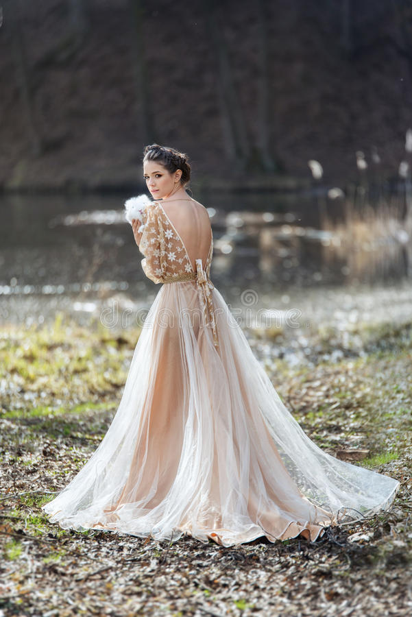 Retrato de la mujer que lleva el vestido elegante que se coloca cerca del lago con el conejo en manos fotografía de archivo