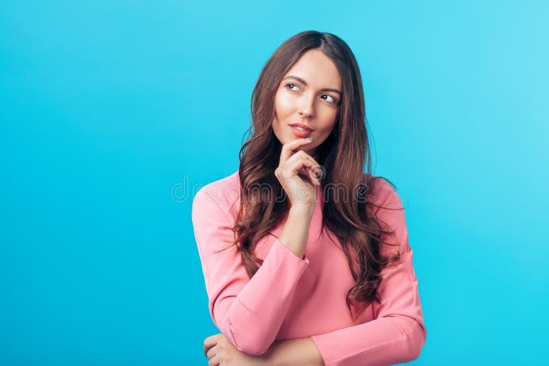 Retrato de la mujer que se pregunta pensativa que parece de lado aislada sobre fondo azul foto de archivo