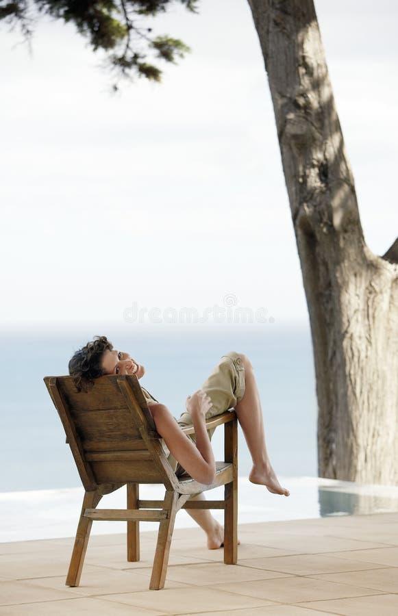 Retrato de la mujer que se relaja en sillón por la piscina del infinito foto de archivo
