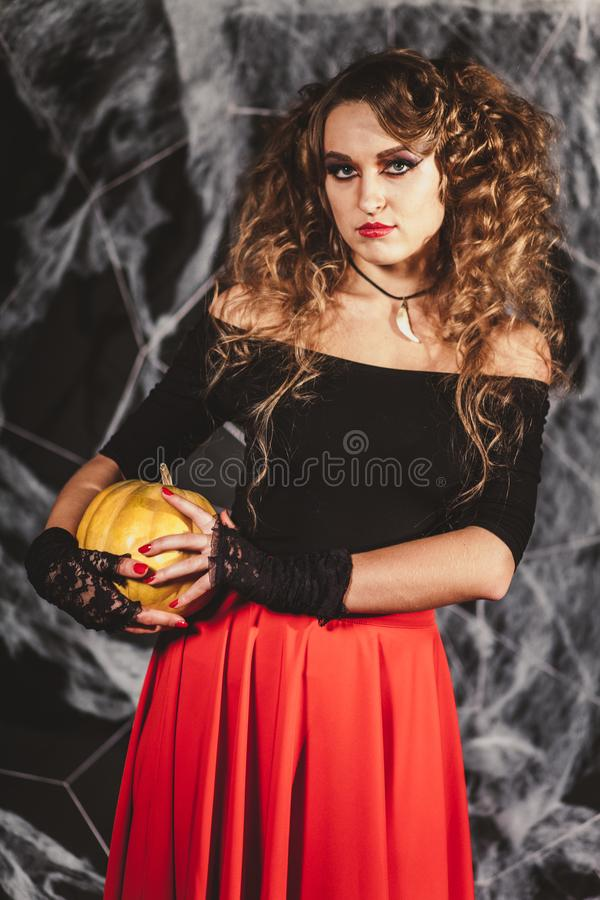 Retrato de la mujer que se sostiene en la calabaza anaranjada de las manos aislada en fondo negro Blusa que lleva y falda roja Ví imagen de archivo