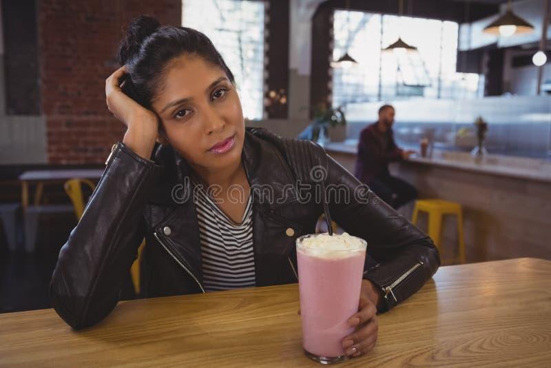 Retrato de la mujer que sostiene el batido de leche de cristal con el amigo en fondo imagenes de archivo