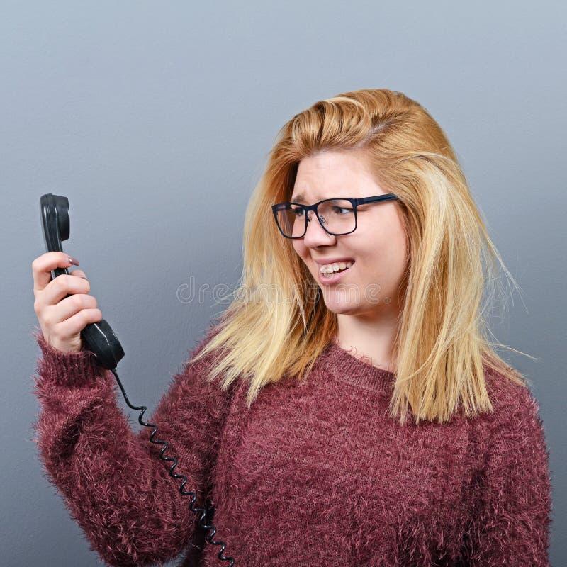 Retrato de la mujer que tiene calll desagradable del teléfono contra fondo gris fotografía de archivo