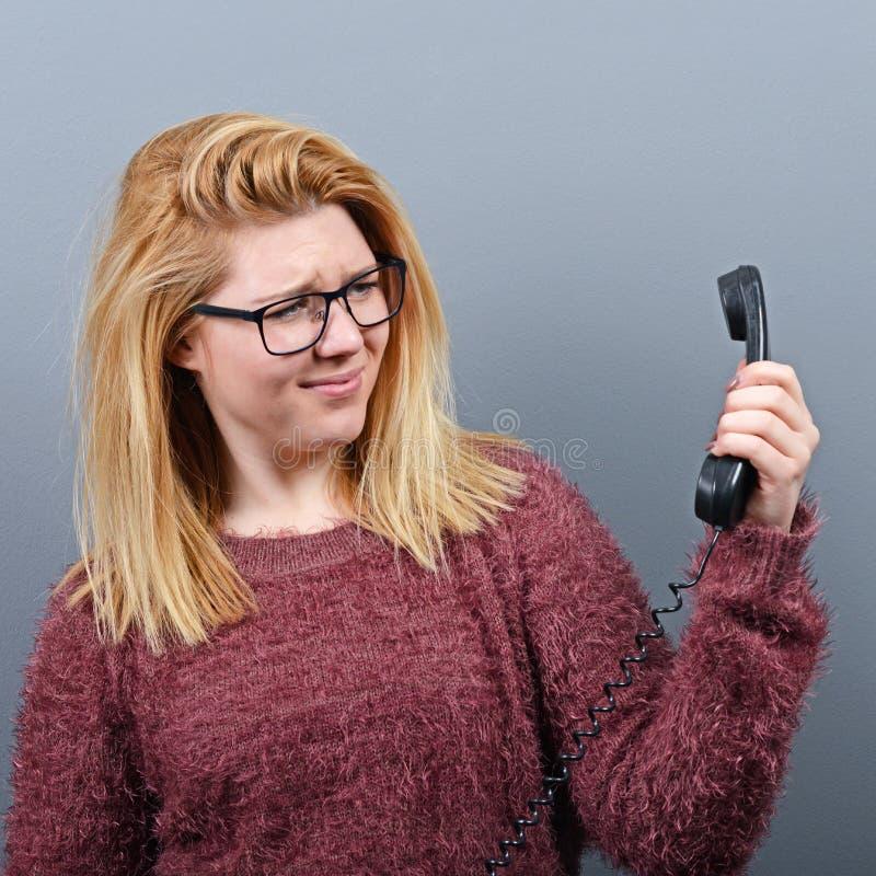 Retrato de la mujer que tiene calll desagradable del teléfono contra fondo gris imagen de archivo libre de regalías