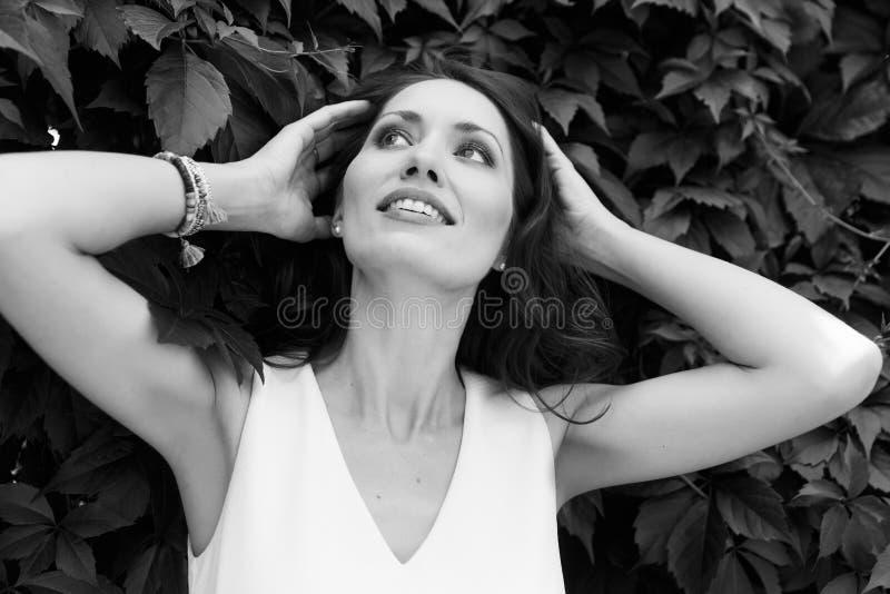 Retrato de la mujer que toca su pelo y que mira para arriba imagen de archivo