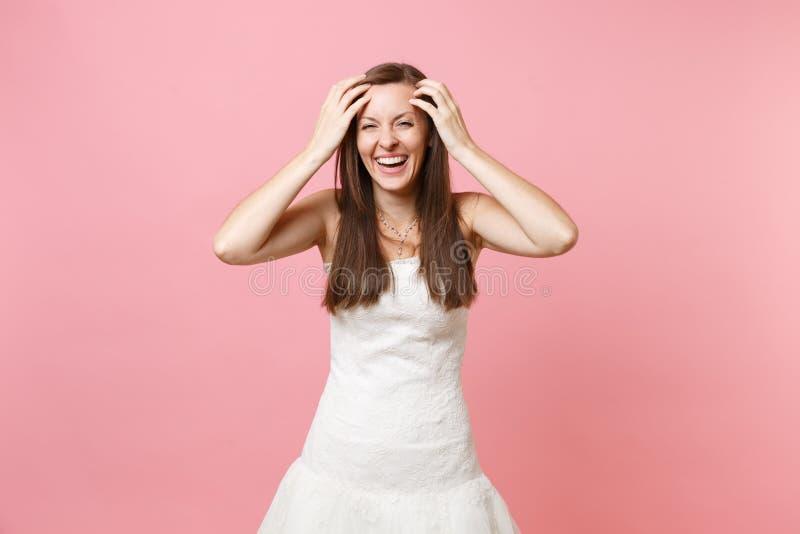 Retrato de la mujer de risa alegre de la novia en la situación blanca hermosa del vestido que se casa que guarda las manos cerca  imagenes de archivo
