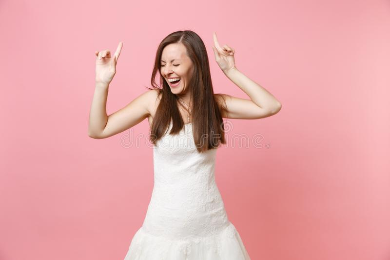 Retrato de la mujer de risa feliz de la novia con los ojos cerrados en el baile blanco del vestido que se casa que destaca los de fotografía de archivo