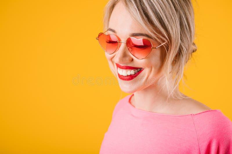 Retrato de la mujer rosada y amarilla Muchacha sonriente en vidrios en forma de corazón fotografía de archivo