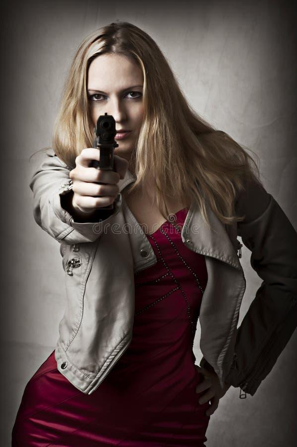 Retrato de la mujer rubia atractiva con el arma de la mano fotografía de archivo