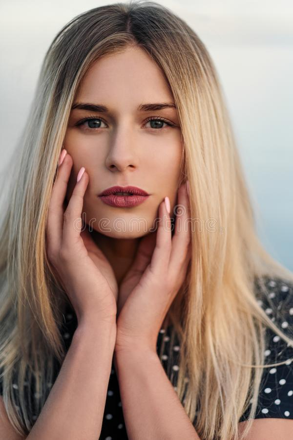 Retrato de la mujer rubia atractiva joven, en un vestido azul al aire libre, manos en cara imagen de archivo libre de regalías