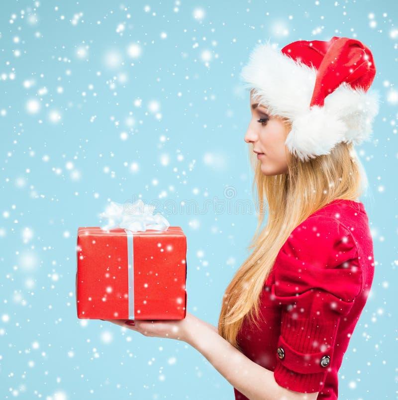 Retrato de la mujer rubia atractiva sobre fondo de la Navidad con nieve imagen de archivo