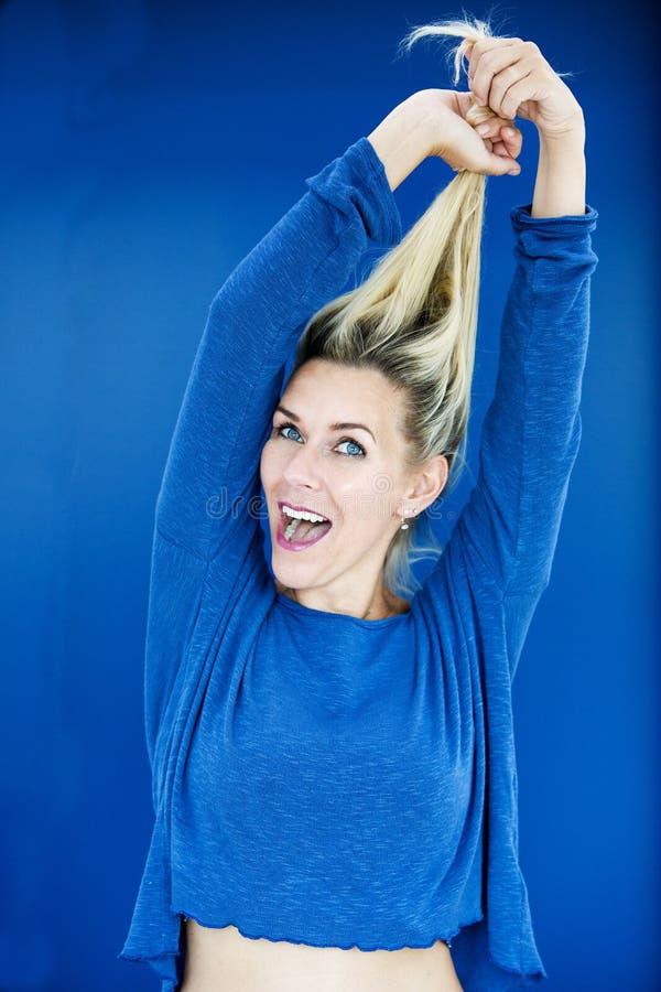 Retrato de la mujer rubia en suéter azul imagen de archivo