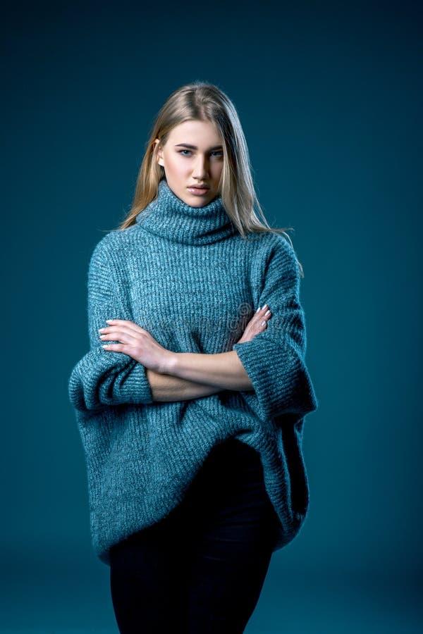 Retrato de la mujer rubia hermosa adentro en el suéter blanco sobre fondo azul gris imagenes de archivo