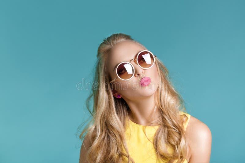 Retrato de la mujer rubia hermosa en gafas de sol y camisa amarilla en fondo azul Muchacha que envía beso del aire imagenes de archivo