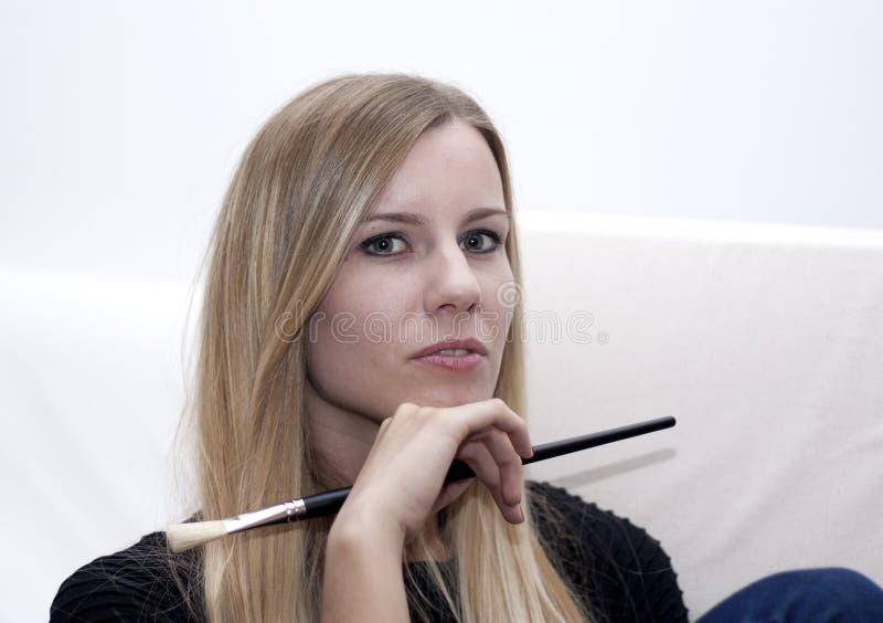 Retrato de la mujer rubia joven con el cepillo del maquillaje fotos de archivo