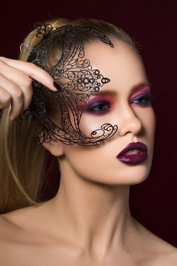 Retrato de la mujer rubia joven con la máscara del partido foto de archivo libre de regalías