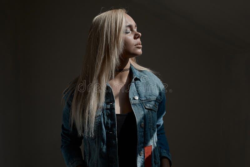 Retrato de la mujer rubia joven en fondo oscuro foto de archivo
