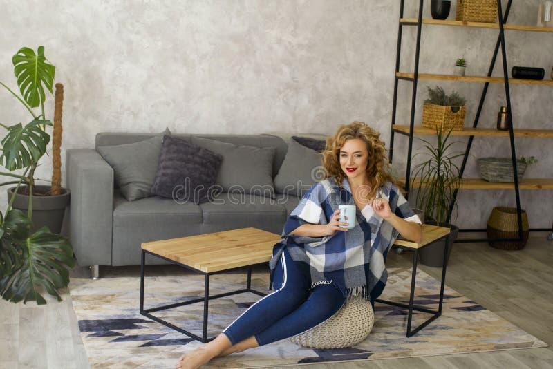Retrato de la mujer rubia joven en la taza de consumición brillante de la sala de estar de té o de café imagenes de archivo