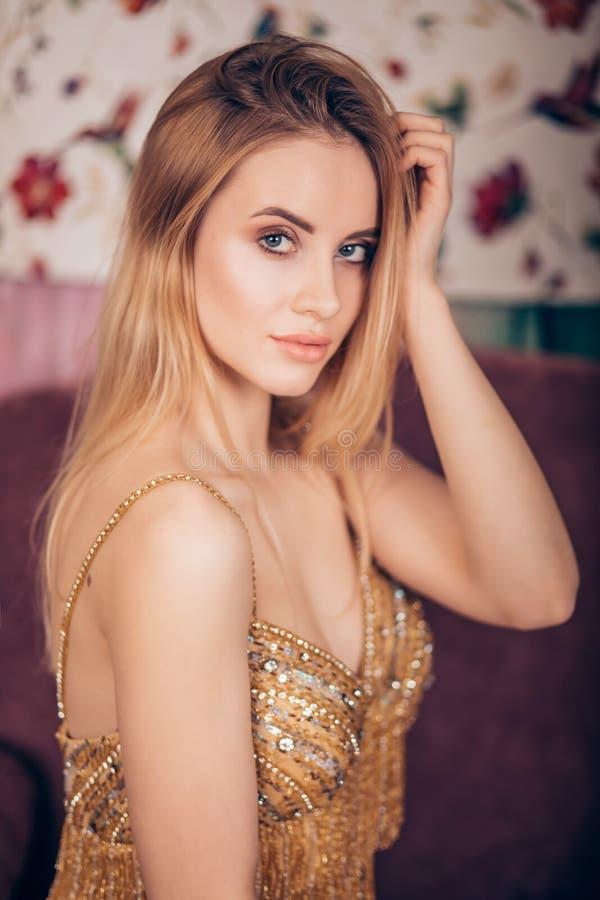 Retrato de la mujer rubia joven hermosa en vestido de oro fotografía de archivo