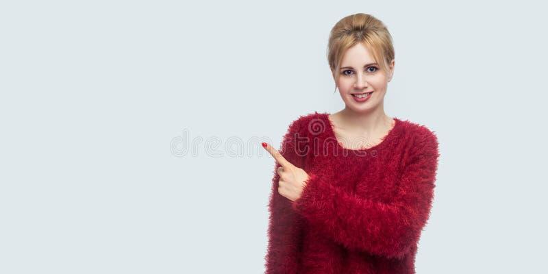 Retrato de la mujer rubia joven hermosa feliz en la situación roja de la blusa, mirando la cámara con sonrisa dentuda y señalando foto de archivo
